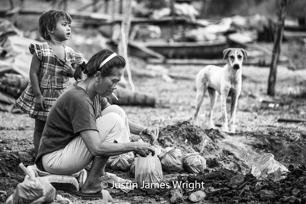 Family Affair   Mercy her granddaughter, even the loyal family pooch are all in on the bagging of coal.  Resilience - The Isla Pulo Community, Philippines.  July 2013. Canon EOS Mk III, EF 100 mm, F 2.8, 1/500 sec.