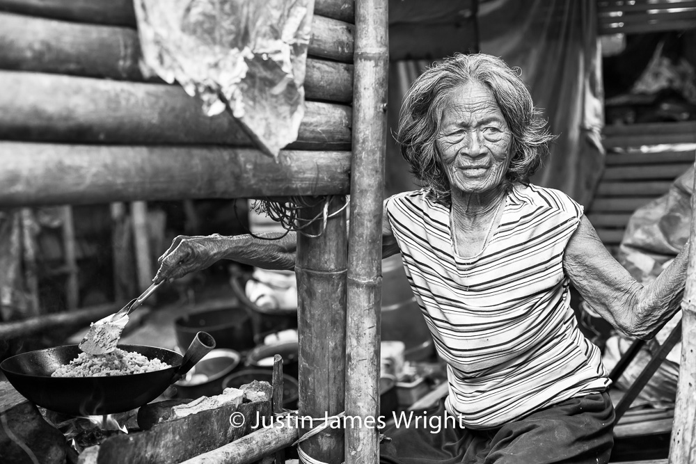 Loreta   The break of day sees her cooking for 6 or 7 (her recollections shift, depending on the day) grandchildren, left in her care. The folds and creases of her skin, a map of 79 years of fortitude.  Resilience - The Isla Pulo Community, Philippines  January 2013. Canon EOS Mk III, EF 50 mm, F 2.8, 1/200 sec.