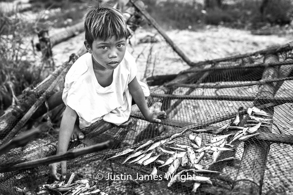 JR   Hair, kissed by the sun, as are fish laid out to dry, this is 4-year-old JR's playtime-meets-work-time.  Resilience - The Isla Pulo Community, Philippines.  July 2013. Canon EOS Mk III, EF 35 mm, F 2.8, 1/320 sec.
