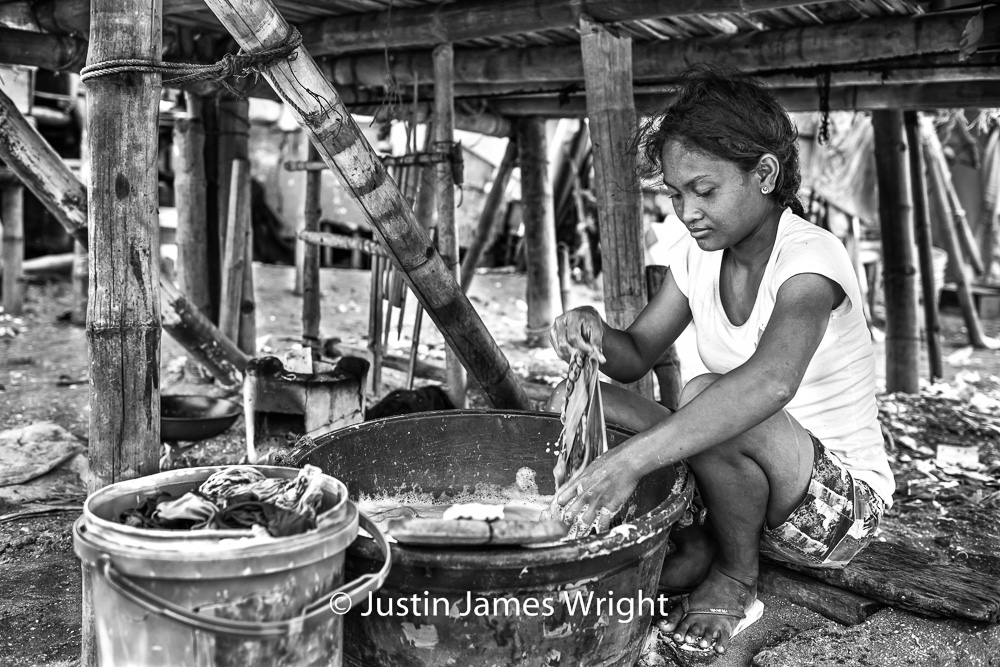 Labandera   Jennifer, 22, winsomely washes clothes. Her hands, in the suds; her head, in the clouds.  Resilience - The Isla Pulo Community, Philippines.  July 2013. Canon EOS Mk III, EF 35 mm, F 2.8, 1/250 sec.