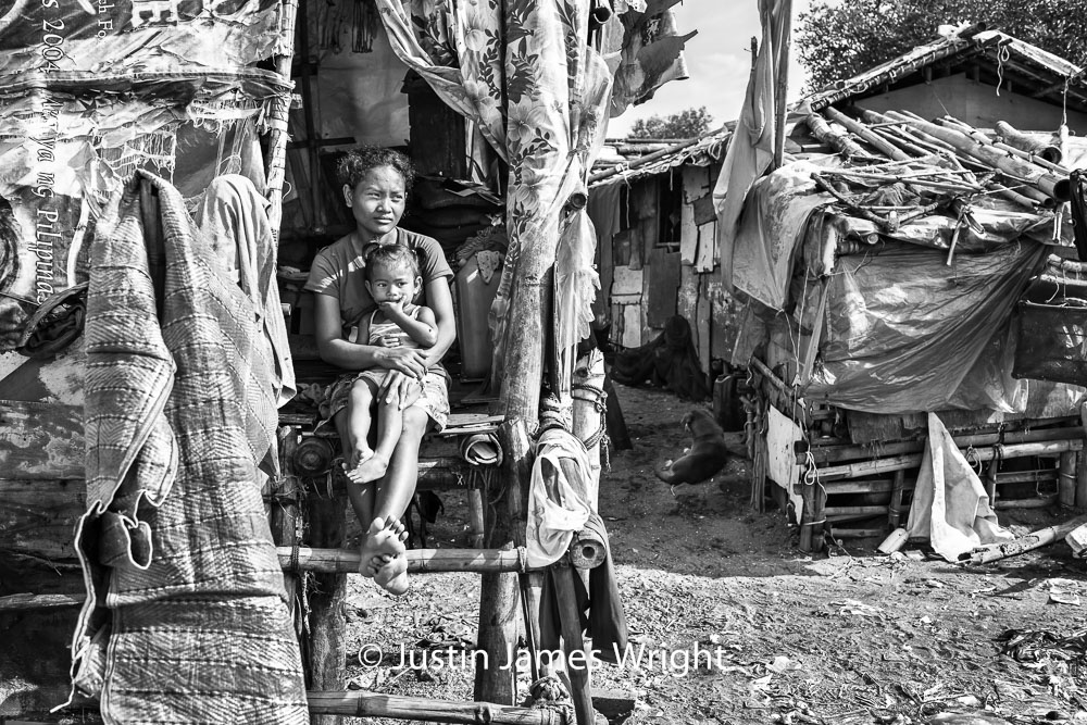 Mag-Ina   Jenna sits, in the safety of mother Jennifer's arms. At the doorway of their simple abode, Jennifer appears lost in thought; 22 years of her life brought to the forefront in this solitary moment.  Resilience - The Isla Pulo Community, Philippines.  July 2013. Canon EOS Mk III, EF 35 mm, F 5.6, 1/400 sec.