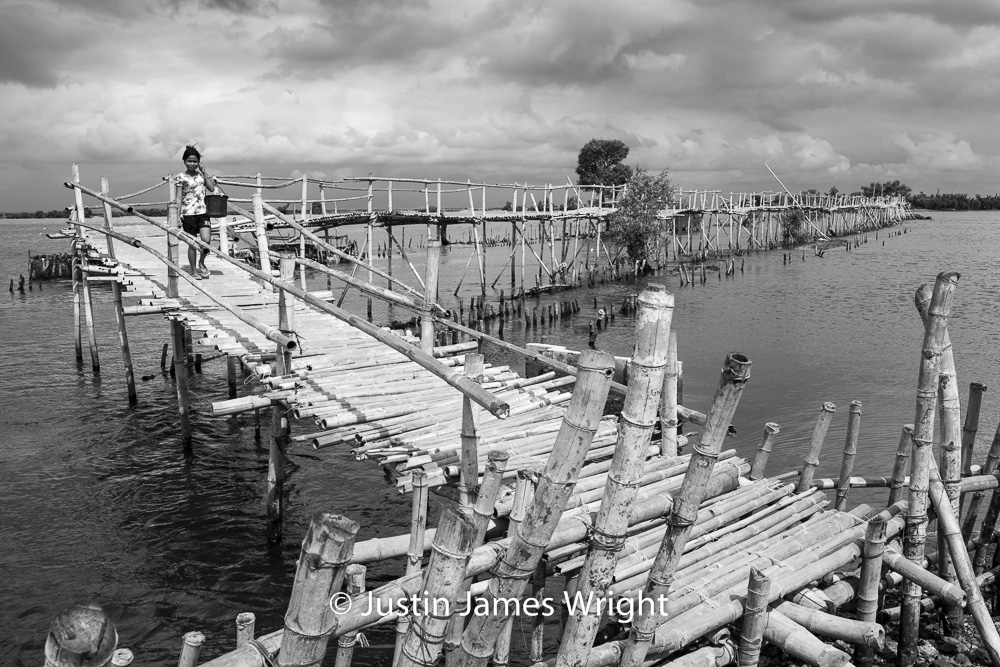 A Vendor travels along the Bamboo Bridge   Resilience - The Isla Pulo Community, Philippines.  July 2013. Canon EOS Mk III, EF 35 mm, F 11.0, 1/320 sec.