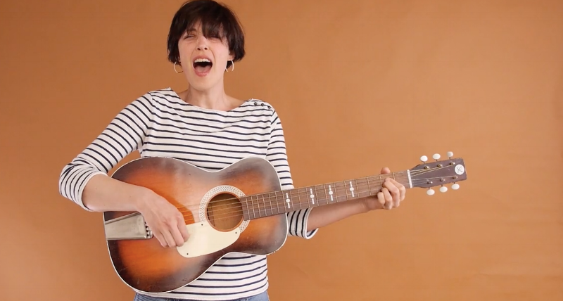 Katie Ha Ha Ha plays guitar in video still