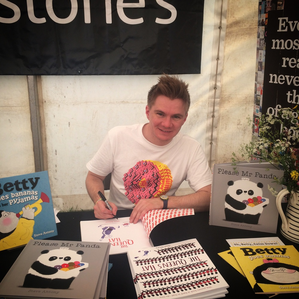 Signing books in the tent.