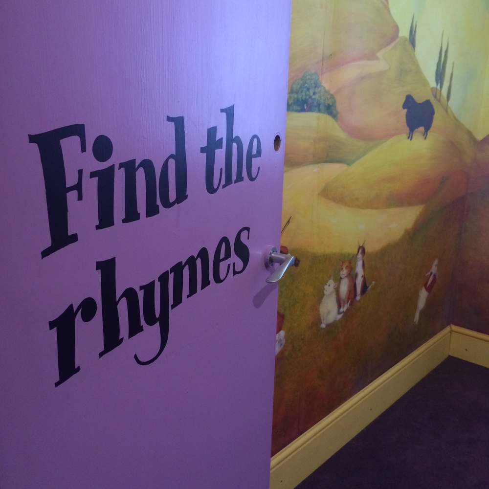I entered the rhyming room. On the walls were beautifully painted murals, by...