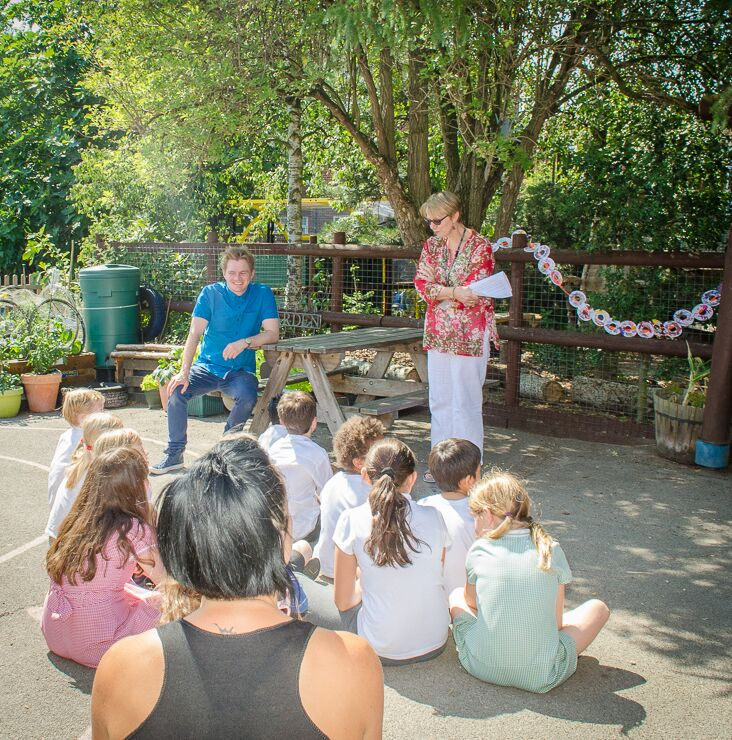 Head Teacher, Ms Susan Adams, gives a speech before handing me the scissors to cut the ribbon of doughnuts. (Photo by Emerson Wimsey)