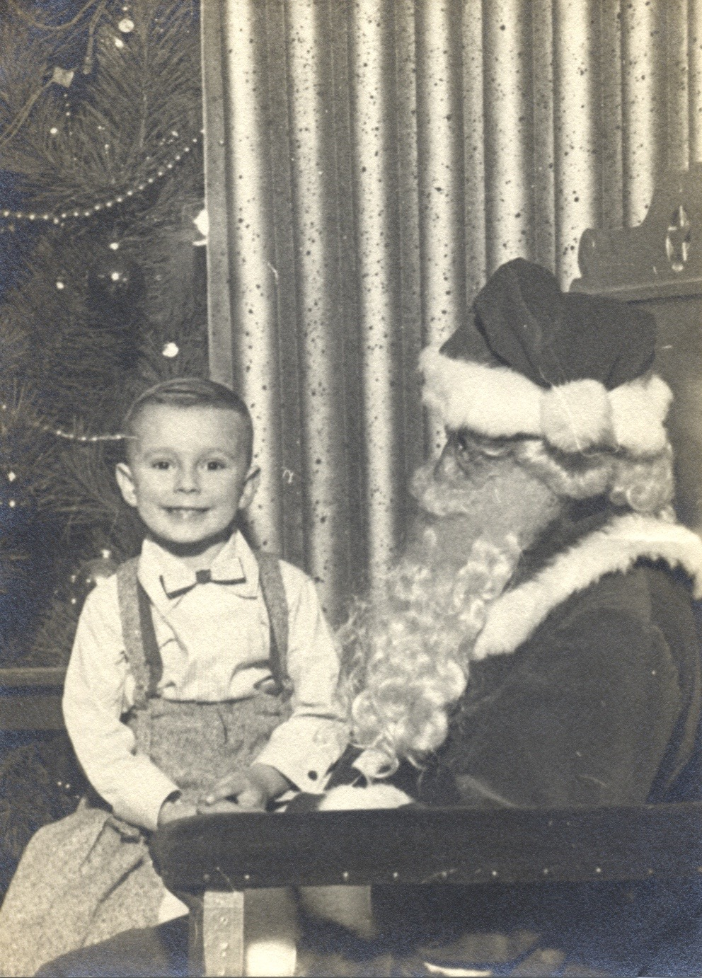 This is me with one of Santa's helpers, or so I thought. I think it's from December 1953, making me four at the time.