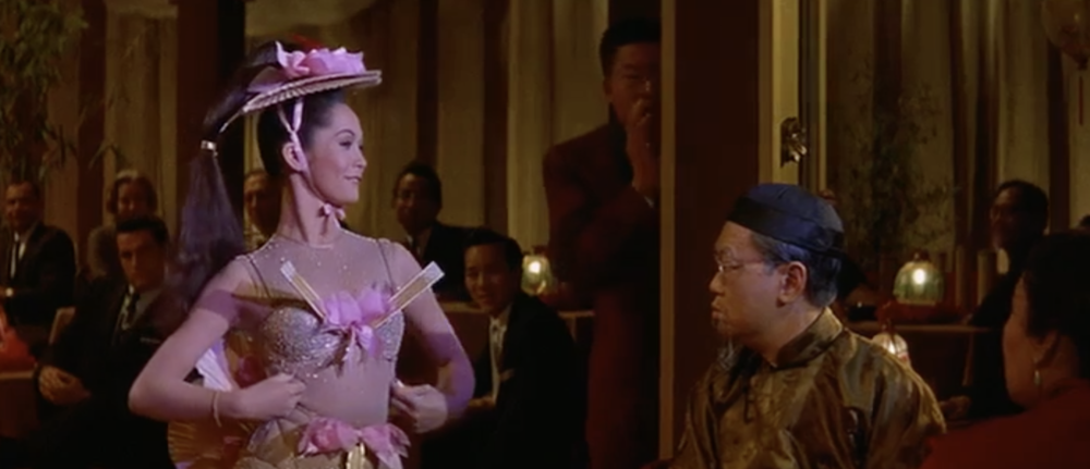 Nancy Kwan as Linda Low revealing a little too much of herself for Master Wang (Benson Fong)