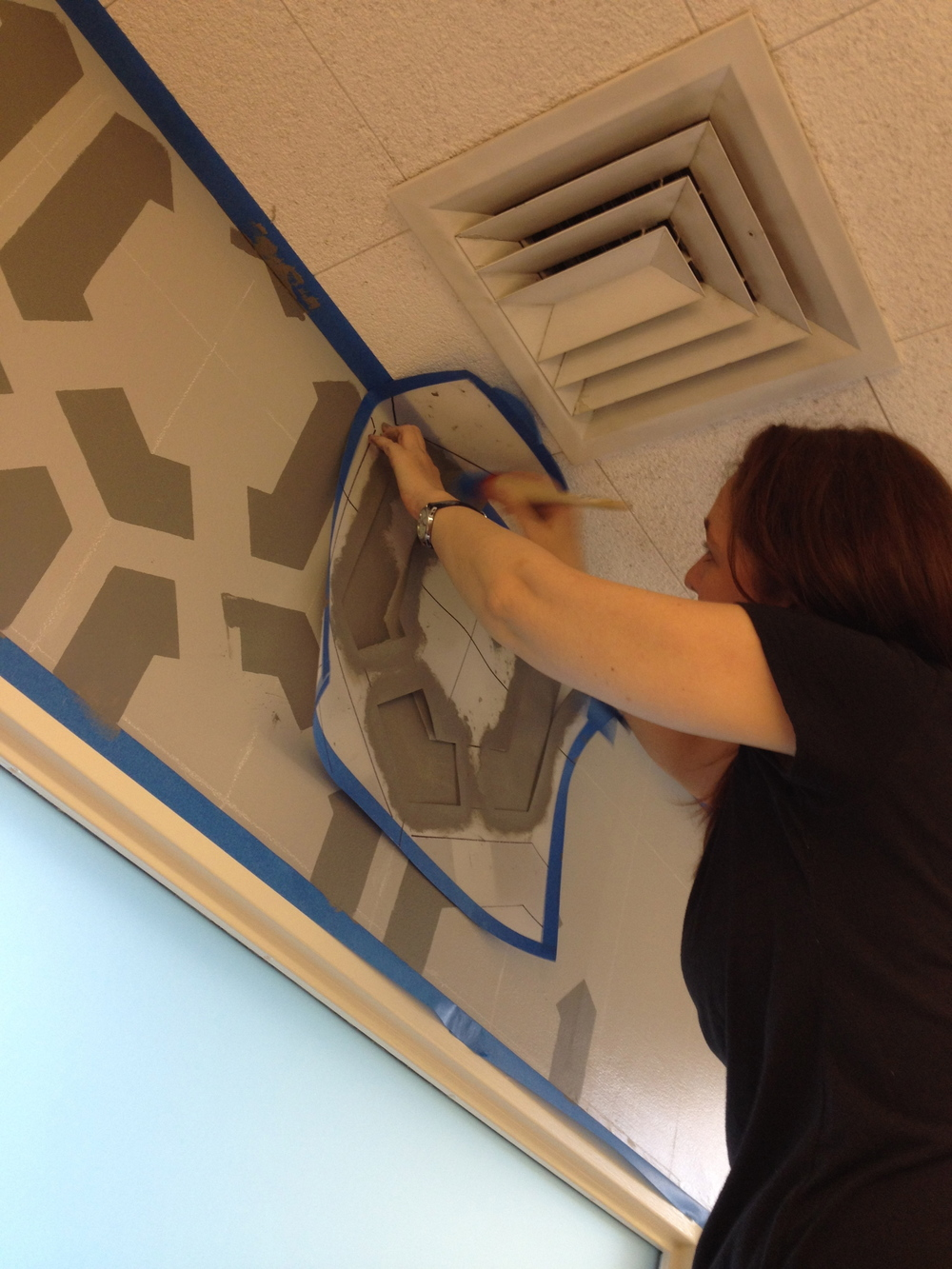 Junior muralist Shannon Geis hanging off of a tall ladder to get the design to meet the ceiling.