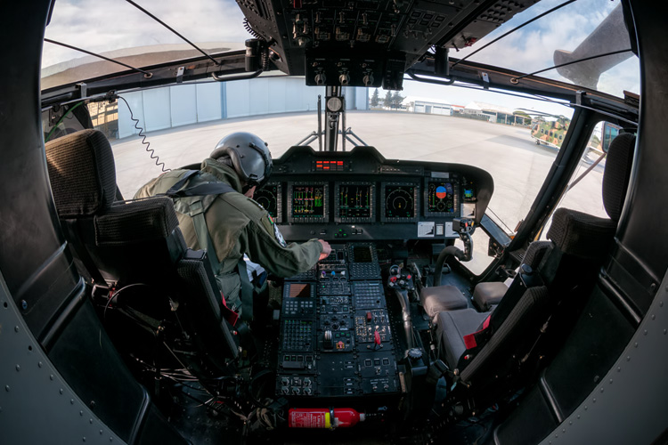Tha vast array of buttons & switches, MFD's (Muli function displays) FLIR & controls and the flight controls (cyclic, collective and tail rotor pedals) of the AW101/EH-101 are all visible as Gouveia begins the pre flight checklist.