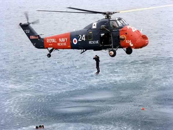 771 NAS Wessex as a rescue swimmer/diver launches himself into the water. Copyright of the Royal Navy/MOD.