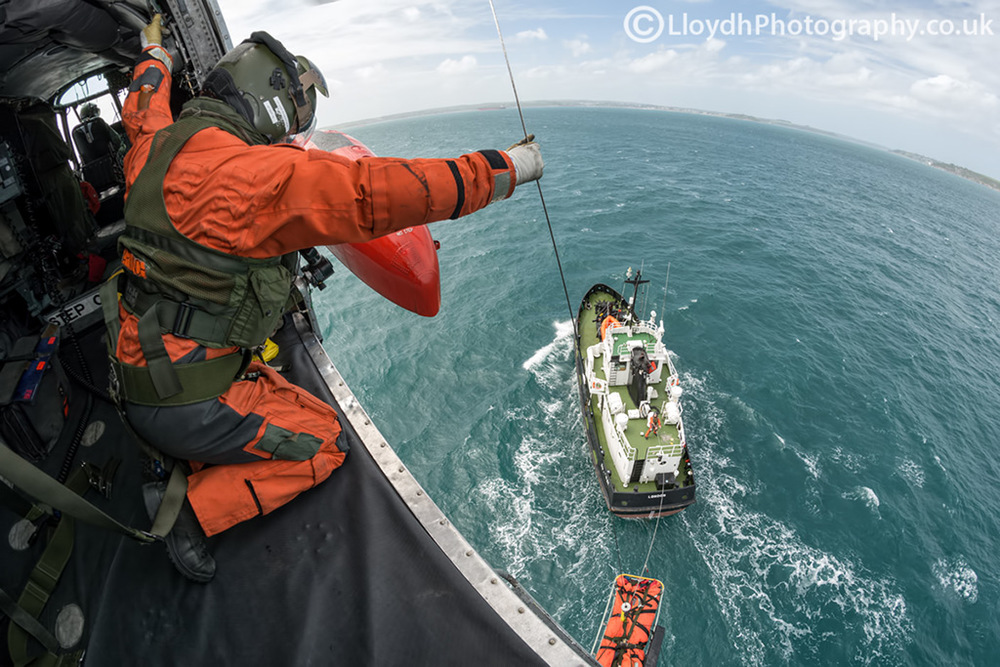 Pilot, winch operator and aircrewman all pictured in one photo as they conduct winching ops with a civilian vessel off the coast of Cornwall.