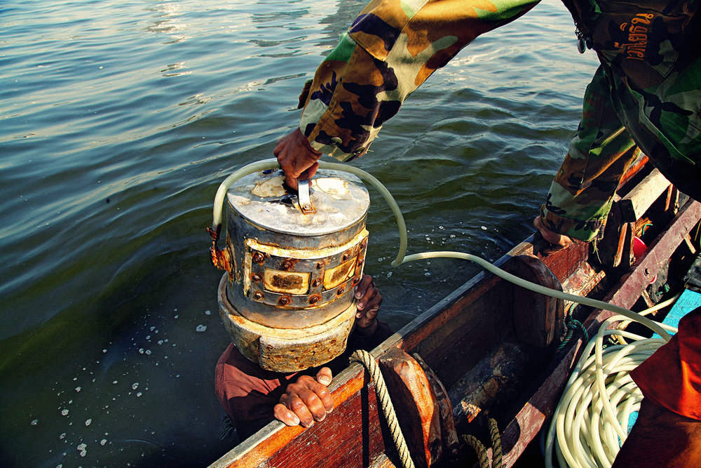 """Treasure Hunters In the Chao Phraya river a couple of long tail boat sail to the middle of the river and send a diver in the muddy 5 meter depth of the river to collect """" treasure"""""""