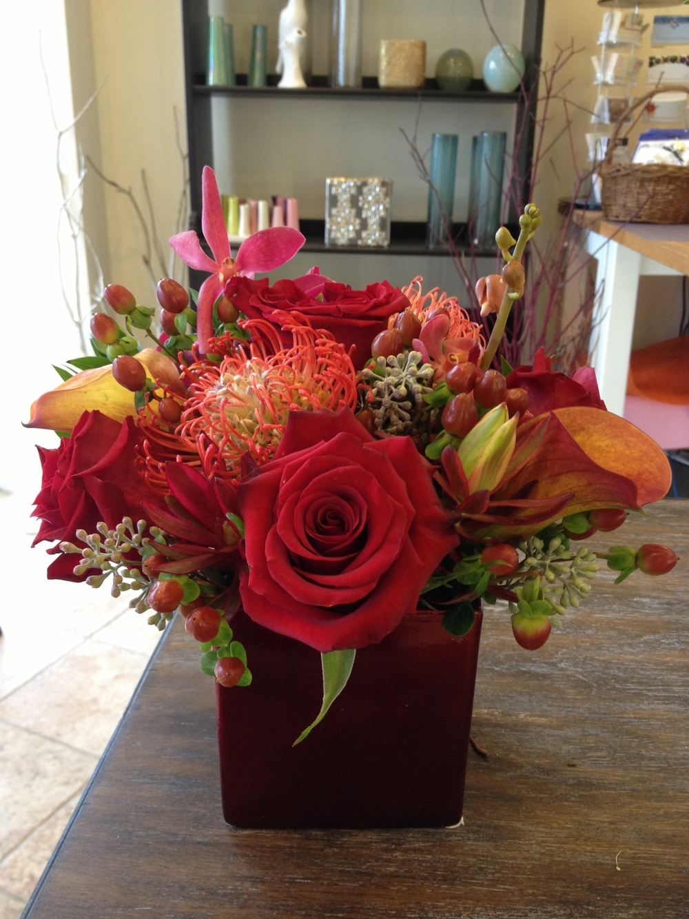 Orange calla lilies, magenta orchids and pincushion protea complement dark red roses in this Bloomsbury Park design.