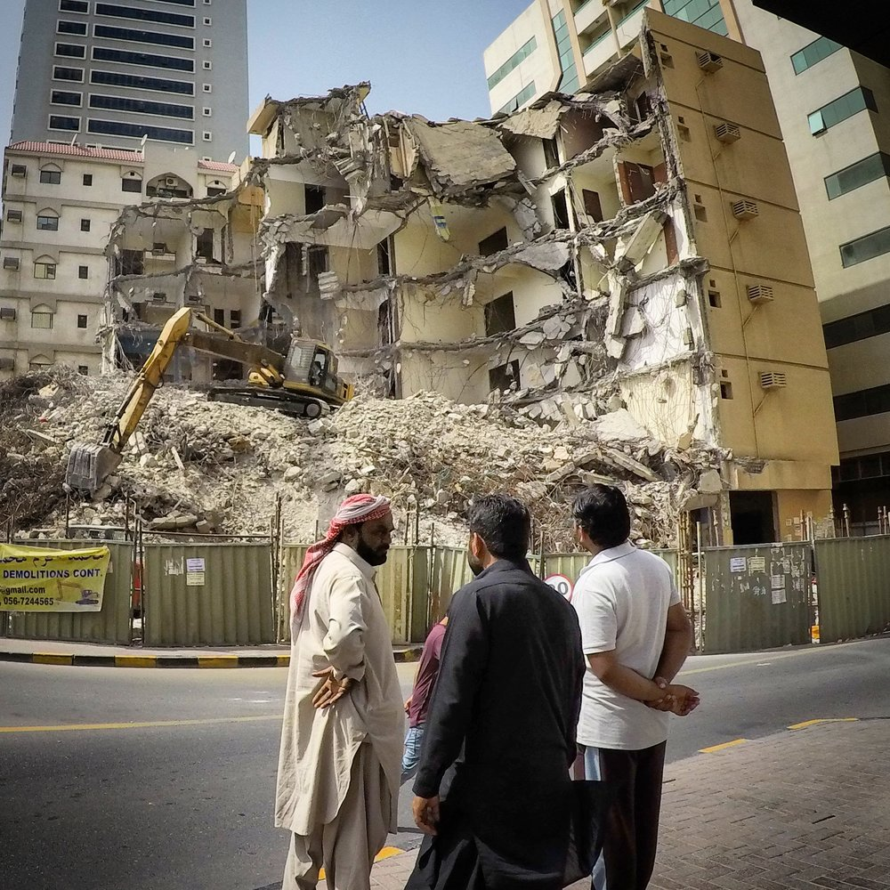 Men watching demolition of a building, Sharjah - United Arab Emirates