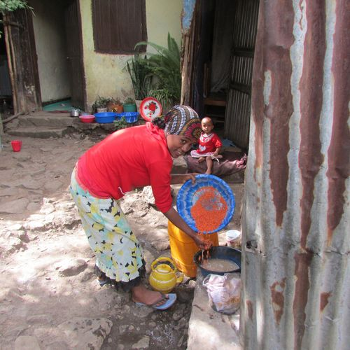 Neighbor girl rinsing lentils and caring for her younger sister