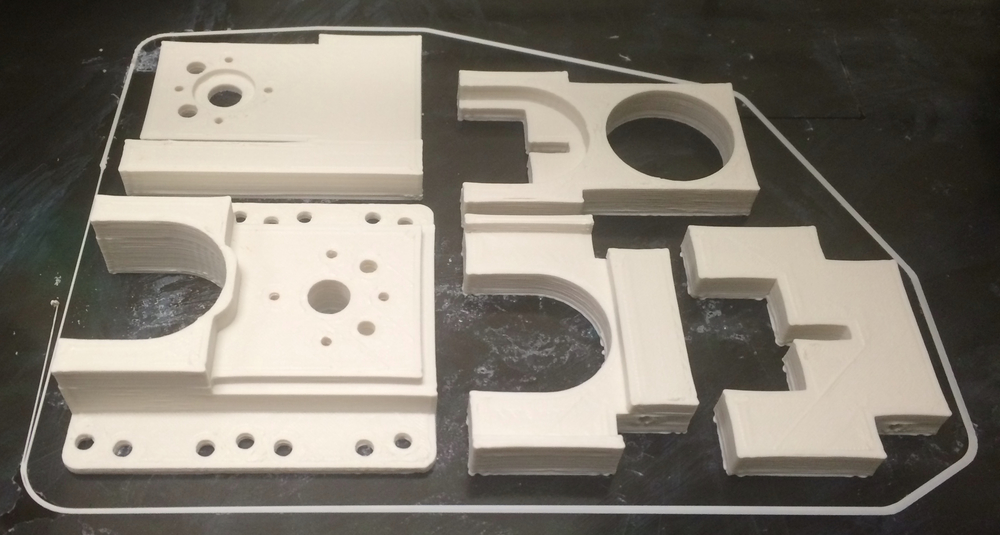 CUSTOM PARTS ON THE BED OF 3D PRINTER. THE MID MOUNT AND PLUNGER UNIT WERE BROKEN INTO SEPERATE PARTS FOR PRINTING AND REASSEMBLED LATER.