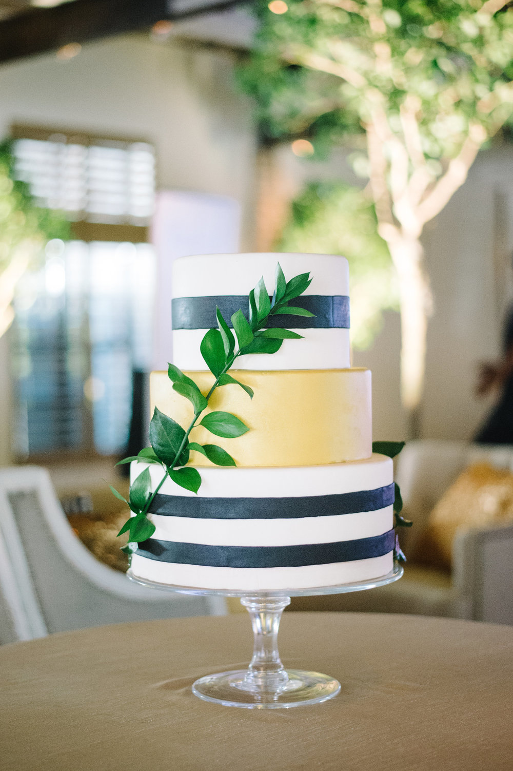 black-and-white-striped-caked-with-gold-center-and-greenery-wrapping-around-charleston-delicious-desserts-the-knot-market-mixer-cannon-green