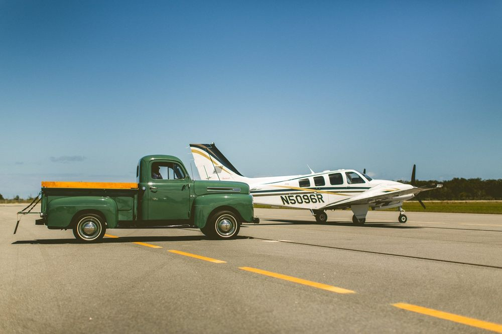 bride-and-groom-exit-by-vintage-truck-airplane
