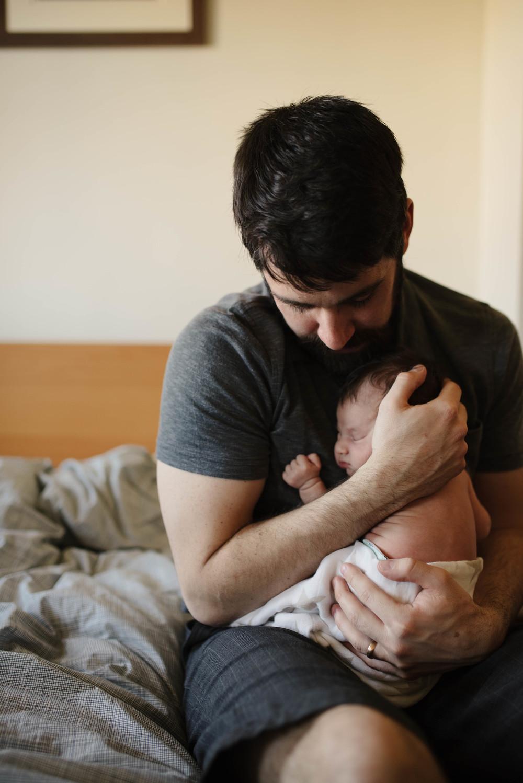 dad cuddling newborn photo
