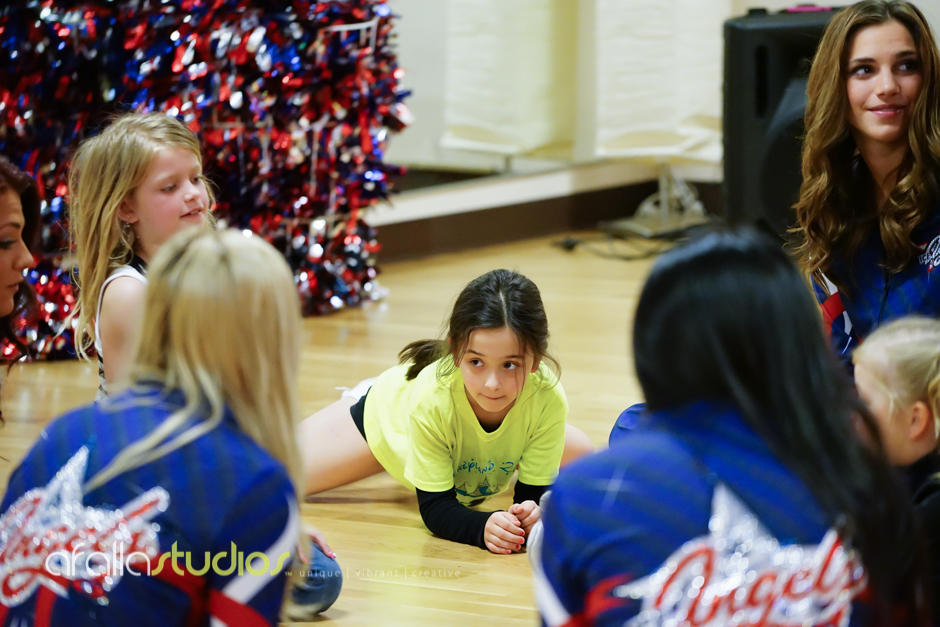 One of our Junior Ice Angels stretching and chatting with their big sisters, the Allen American Ice Angels.