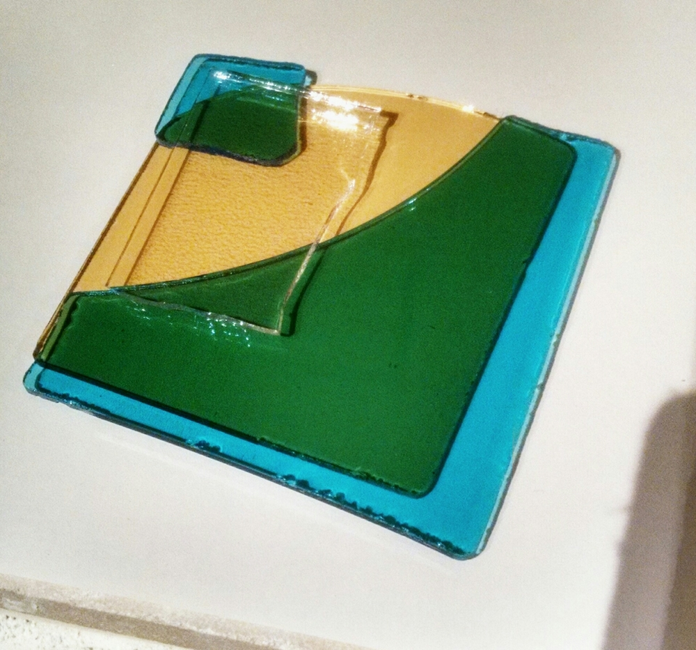 The edge to the right sites that the glass is actually blue, until layered on top of yellow...blue+yellow=green.
