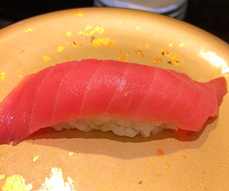 Den mellanfeta delen av tonfisken är både grann och god. Den guldfärgade tallriken signalerar dyrare fisk på den roterande sushi-krogen.