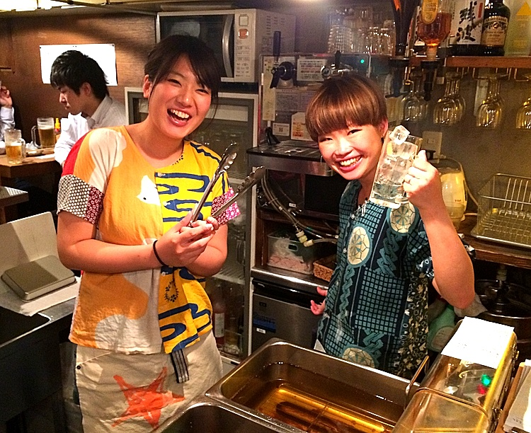 Yuna (med långt u) och Yumi friterar kyckling och blandar grogg i brinnande fart men hinner ändå alltid med att konversera med gästerna. Typisk japansk småkrogsmiljö.