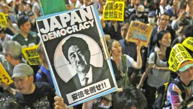 """Regeringen Abe ändrar """"tolkningen"""" av grundlagen för att tillåta japansk militär att engangera sig i väpnad konflikt utanför Japans gränser. Med Japanmått mätt stora protester igår. Under bilden av Abe med Hitler-mustasch står det """"Störta Abe"""".  Bild: TV-bild från Aljazeera"""