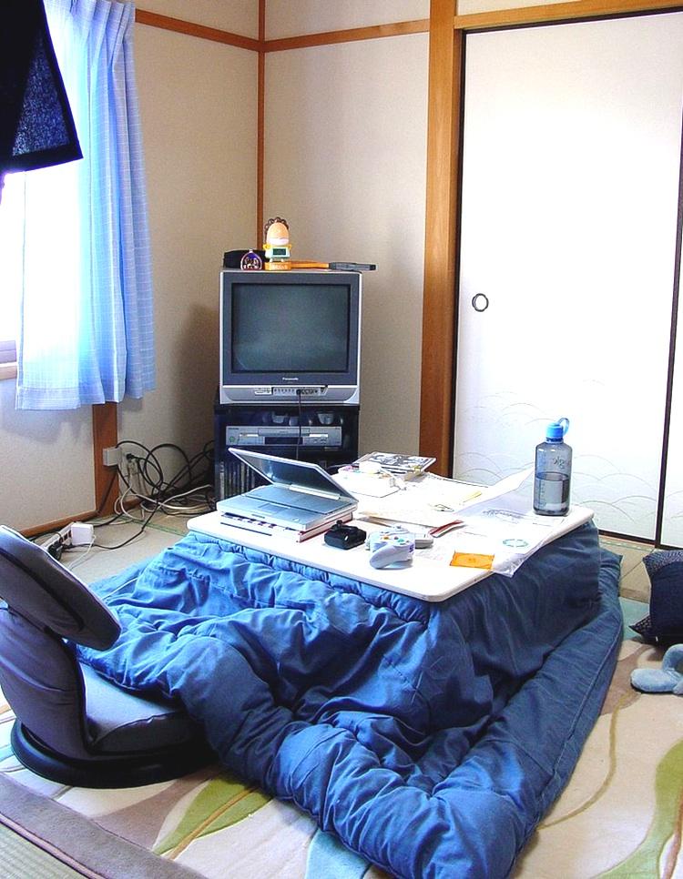 Här ser vi en sk  kotatsu , ett lågt bord med värmelampa på undersidan och ett stort täcke inklämt mellan dubbla bordsskivor. Mattan under har inbyggd elvärme.  Foto:  Tasteful TN . Creative Commons