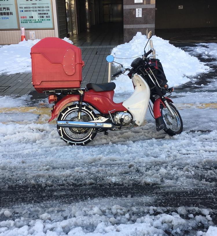 Oavsett väder så ska posten levereras. Här är lokale brevbäraren ute med sin pålitliga Honda Super Cub. Lägg märke till den robusta snökedjan på bakdäcket