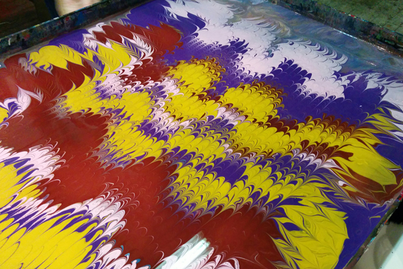 Acrylic paint floating on gelled water surface after combing tools have been dragged through it.
