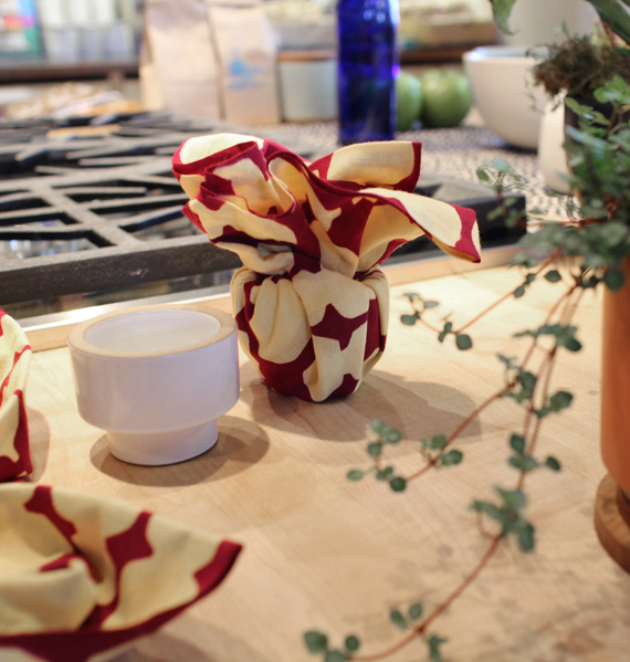 Magumi took inspiration from the shape of the candle holder by tucking the fabric into it's cavity and creating a flower with the ends. This is a great example of letting the object dictate how the fabric forms around it. Maybe this will work for wrapping a small cup too!