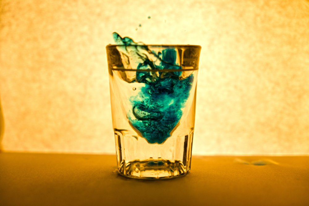 rising bubbles in a shot glass photography by Austin Smith