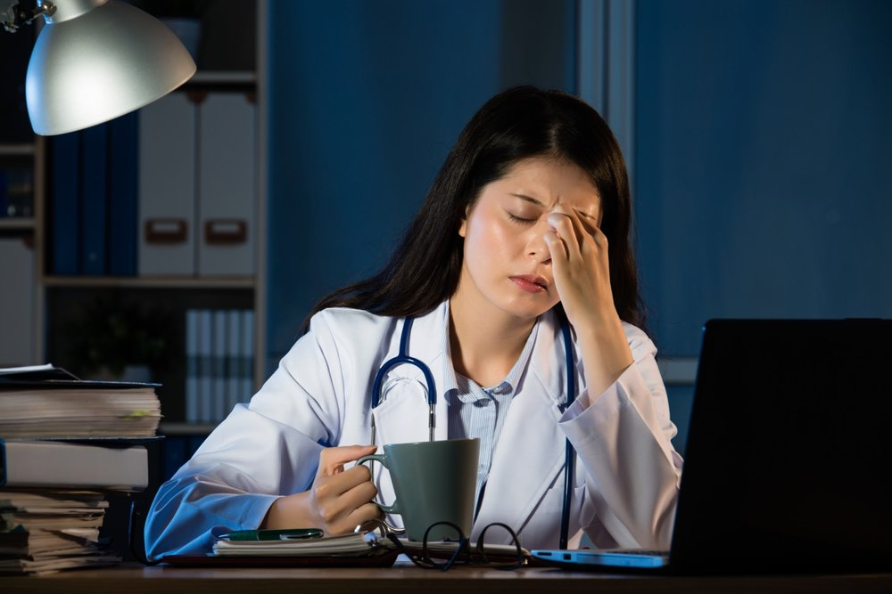 unhappy doctor with headache stressed holding coffee.jpg