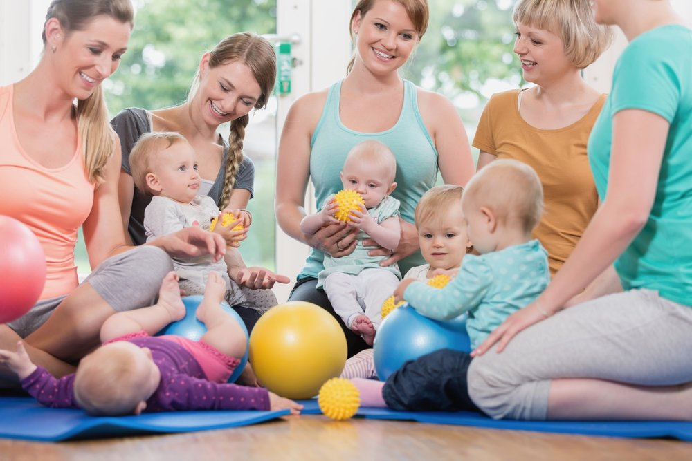 Young women in mother and child group playing with their baby kids.jpg
