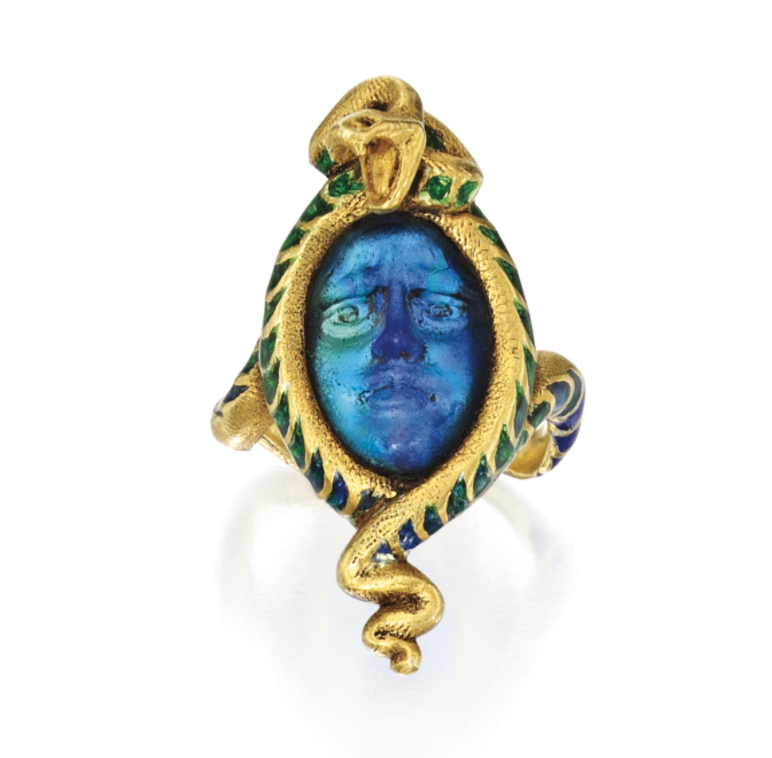 An 18 Karat Gold, Molded Glass and Enamel Ring, René Lalique, France    Designed as a greenish blue glass face of Medusa, with blue and green enamel scales applied to the snake, gross weight approximately 10 dwts, size 8, signed Lalique, with French maker's mark; circa 1900.     Estimate : USD 15,000 — 20,000   LOT SOLD  SEPTEMBER 2016 .  USD 322,000 (Hammer Price with Buyer's Premium) -  Photo Courtesy of Sotheby's