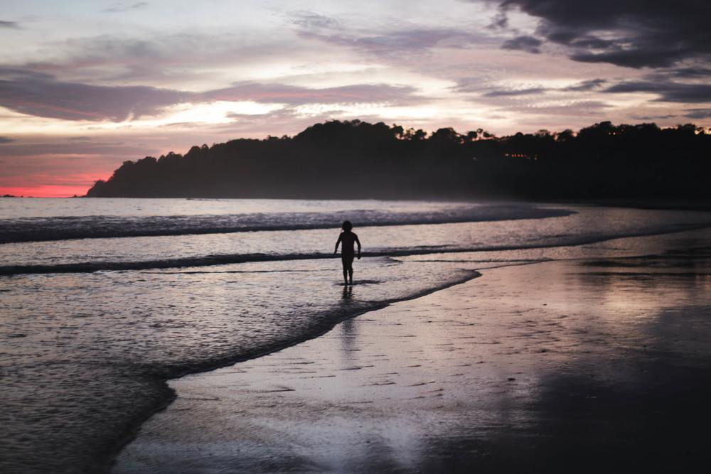A little girl plays on the beach at sunset in Manuel Antonio.