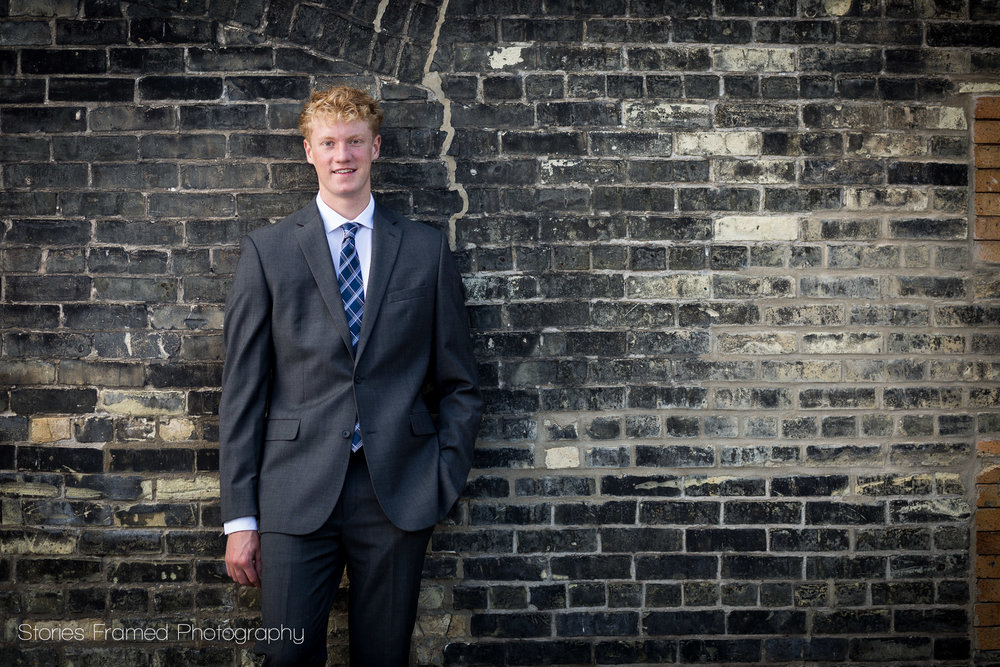 Joe-senior-portrait-classof2018-standing-at-brick-wall-in-MKE