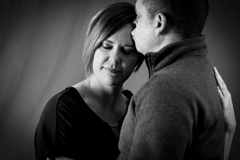 man and woman with eyes closed embracing bw