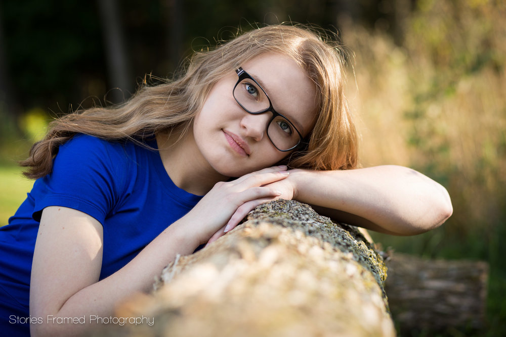 high school senior with glasses leaning on a log