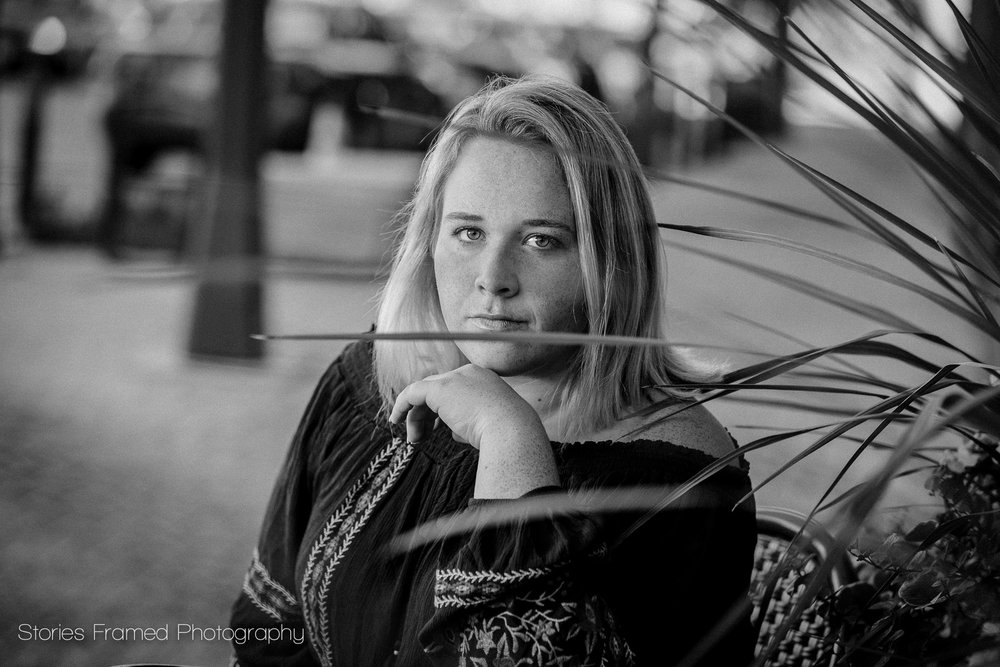 senior portrait of girl behind plant black and white