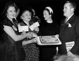 "1950 Grand National Bake-Off, NYC The Duchess of Windsor, second from right, the former Wallis Simpson, congratulates winners of the Pillsbury Grand National Bake-off. From left are Mrs. Bernard Derousseau of Rice Lake, Wis., who won a $5,000 first prize in a junior division of the bake-off, and Mrs. Peter Wuebel, of Redwood City, Calif., winner of the $25,000 first prize in the bake-off. The women are joined by Philip W. Pillsbury, president of Pillsbury Mills, who along with Wuebel, holds the ""Orange Kiss Me Cake,"" which won the top prize. Photo, The Associated Press"