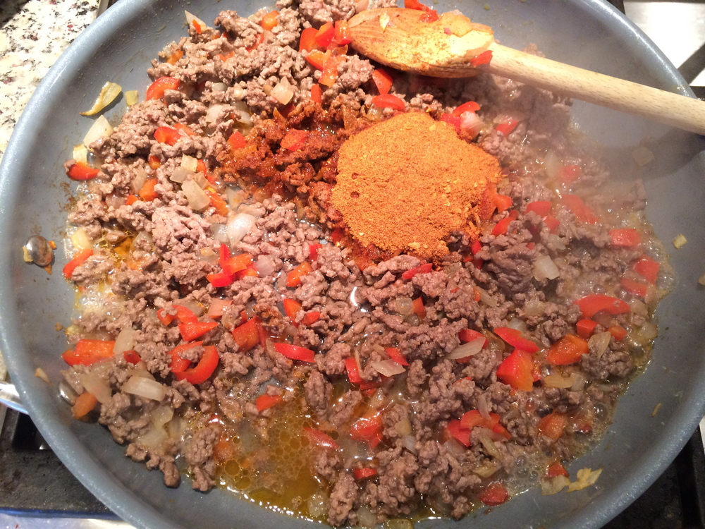 Brown ground beef with the pepper and onions, then add taco seasoning and water.