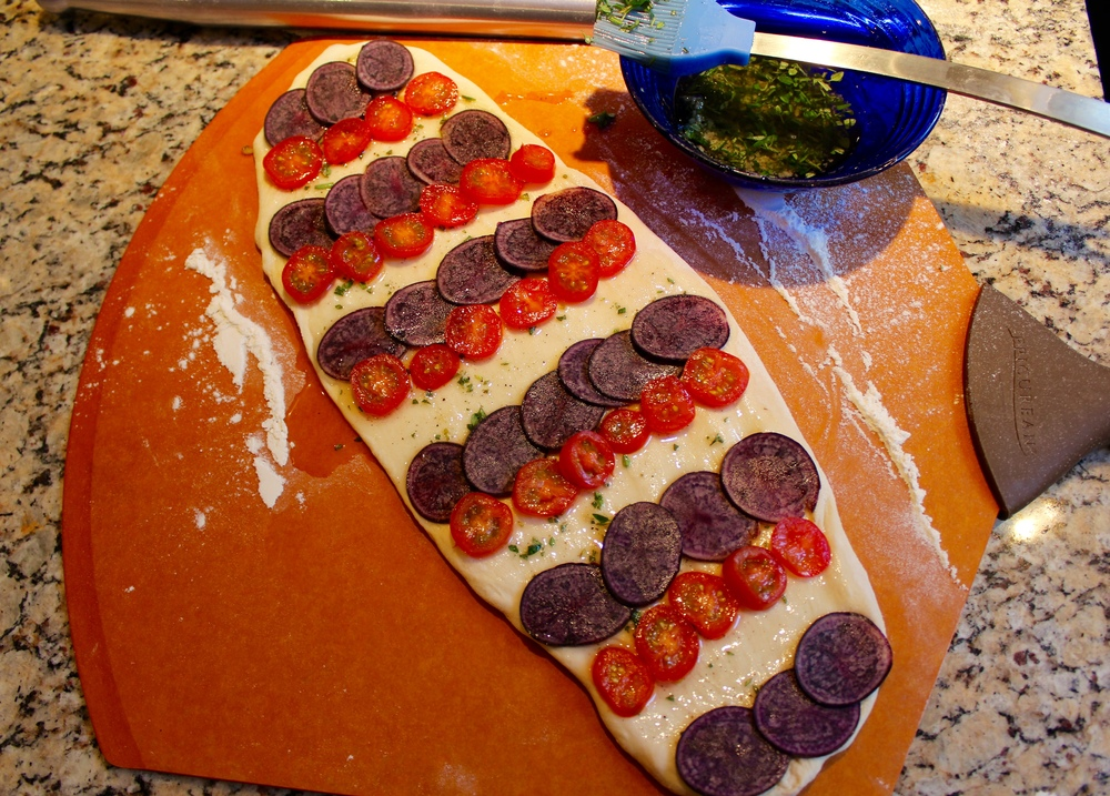 Arrange potato and tomato slices leaving room for goat cheese