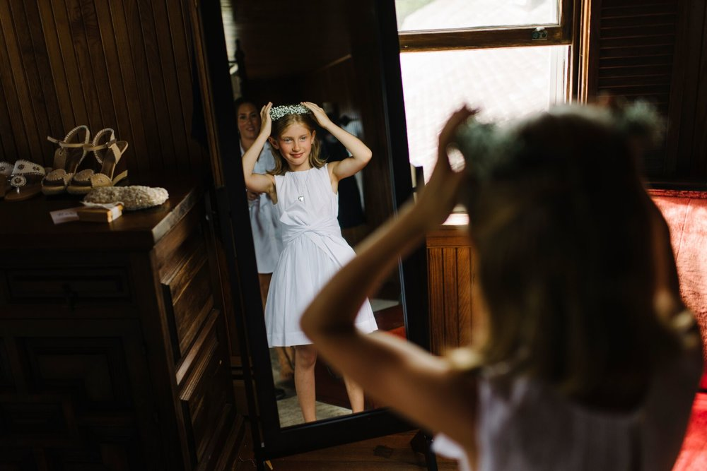 flower girl looking at self in a mirror at cuttyhunk fishing club