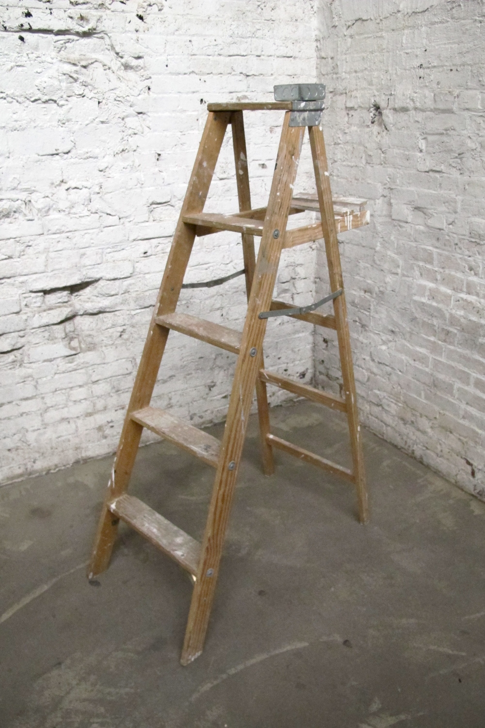 Light brown 4-step wood ladder (paint-splattered)