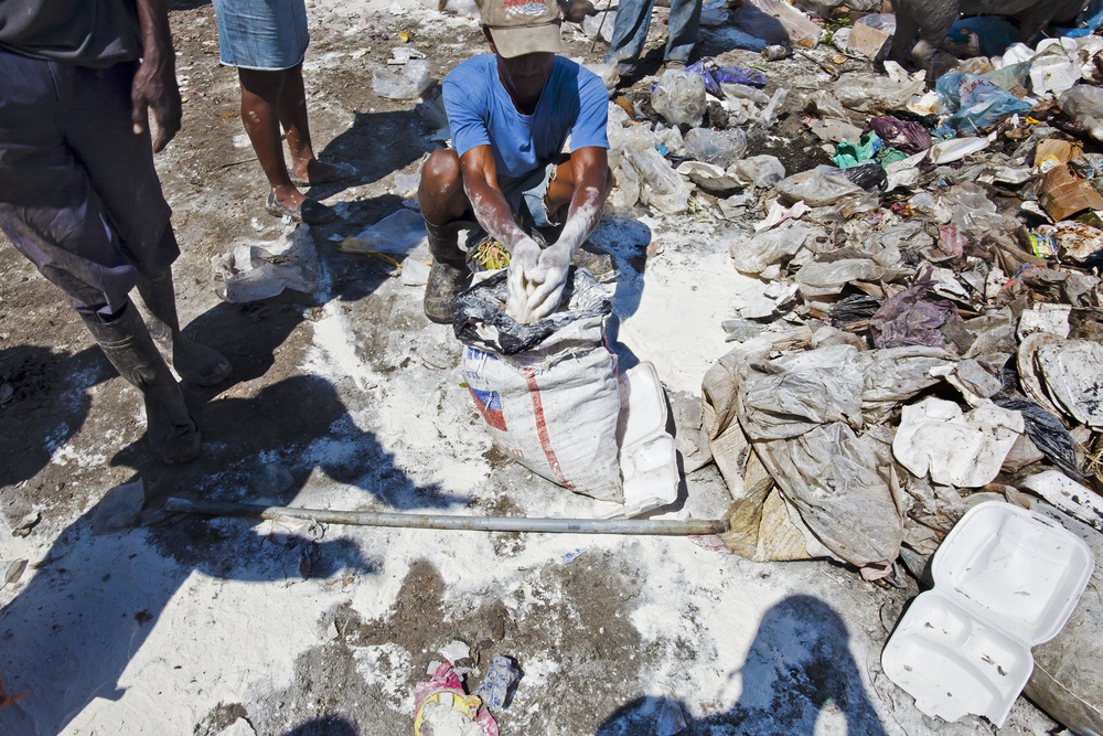 Man scoops up flour in a landfill