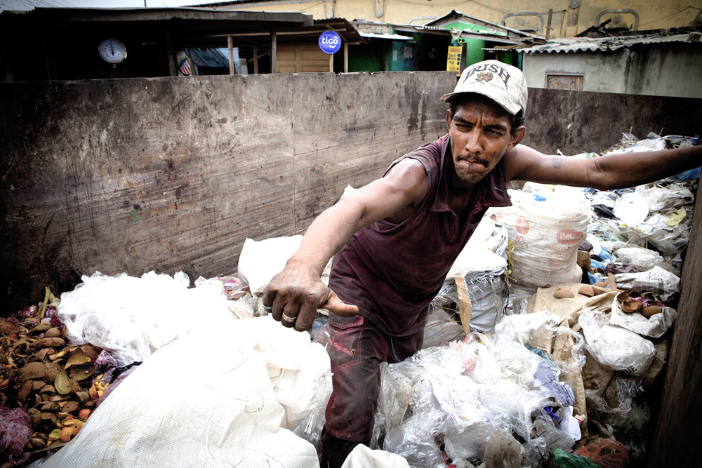 A man sorts through recyclables inside a large dumpster. Barranquilla. Colombia 2014.