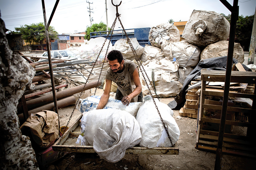A man weighs materials to be sold to Jimmie's business. Barranquilla, Colombia 2014